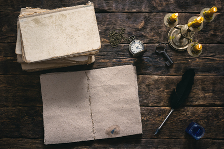 Open blank page book, old literature, pocket watch and a inkwell ...