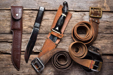 Photo for Hunting knives, leather belts and sheaths on the old wooden table background. Hunting concept background. - Royalty Free Image