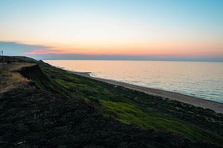 Photo pour Evening sea sunset. Azov sea horizon. Steep slope coast. - image libre de droit
