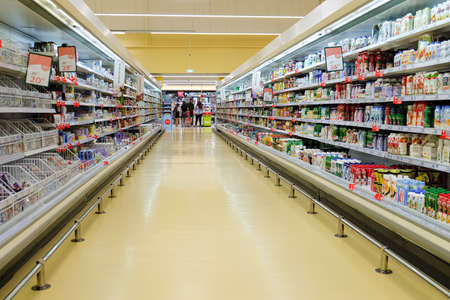 Foto für Belgorod, Russia - July 14, 2019: Long passage with food products for sale, exposed in refrigerators and shelves in Auchan supermarket. Dairy department. - Lizenzfreies Bild