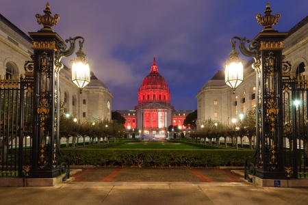 Nighttime view of San Francisco City Hall illuminated by red light.