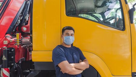 Foto de Close-up photos of Asian truck drivers wearing masks to protect against dust and the spread of the flu. Covid 19. Inside the car front - Imagen libre de derechos