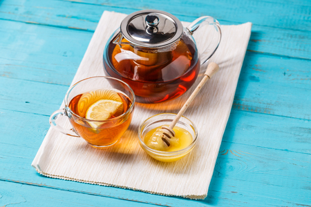 Glass cup of tea with lemon, glass teapot and honey.