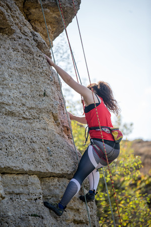 Athlete girl clambering over rock