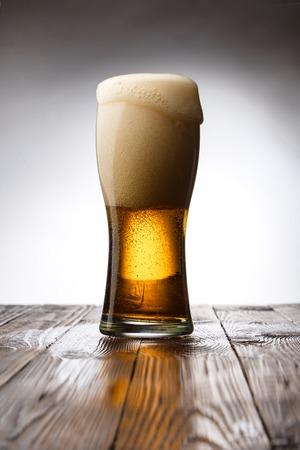 Foto de Frosted glass of light beer on wood table - Imagen libre de derechos