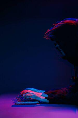 Foto de Hacker in the hood working with computer typing text in dark room. Image with glitch effect - Imagen libre de derechos