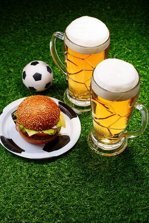 Foto de Two glasses of beer, hamburger and soccer ball on green grass. - Imagen libre de derechos