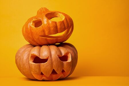 Foto de Photo of two halloween pumpkins on empty orange background - Imagen libre de derechos