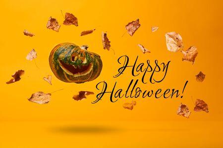 Photo pour Flying pumpkin, dry leaves and inscription Happy Halloween - image libre de droit