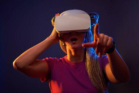 Foto de Woman is using virtual reality headset. Neon light studio portrait. - Imagen libre de derechos