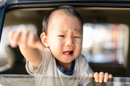 Crying Asian baby in car, safety concept.