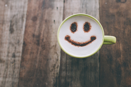 Photo pour Happy face on coffee cup on wooden background with vintage colour effect. Still life. - image libre de droit