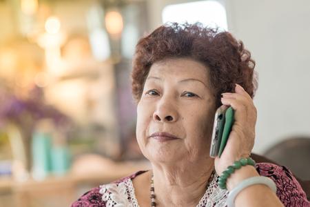 Happy Asian senior woman using smartphone.