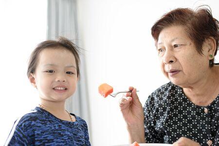 Photo pour Grandmother feeding her child with ripe papaya sliced. - image libre de droit