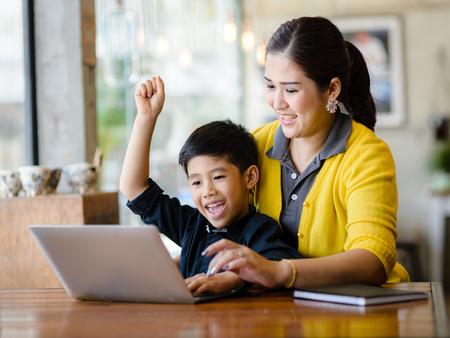 Photo for Happy Asian mother and her son raising their hands while win the online game together. - Royalty Free Image