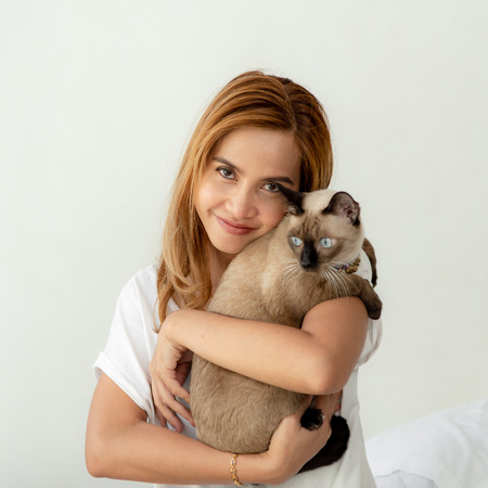 Happy Asian woman holding her cat on white background.