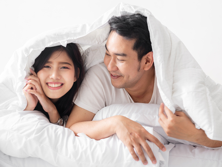 Photo pour Happy Asian couple under white blanket together, lifestyle concept. - image libre de droit