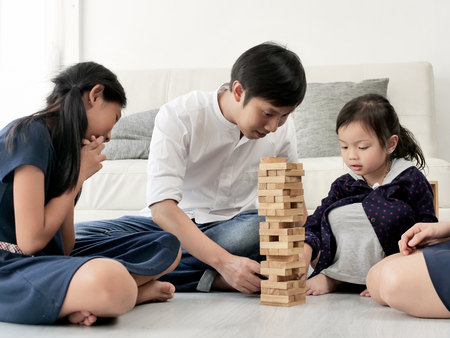 Photo pour Happy Asian family playing wooden blocks together at home, lifestyle concept. - image libre de droit