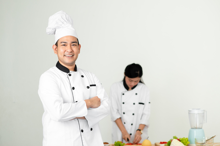 Photo pour Confident Asian chef looking at camera with his helper background - image libre de droit