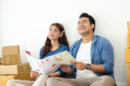 Photo pour Asian couple choosing colour palette for their new house, lifestyle concept. - image libre de droit