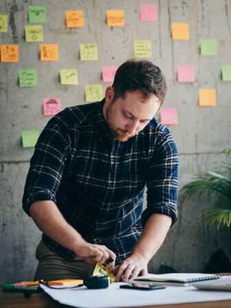 Photo pour Young architecture or engineer working in office with laptop, lifestyle concept.  Sticky notes on cement wall background. - image libre de droit