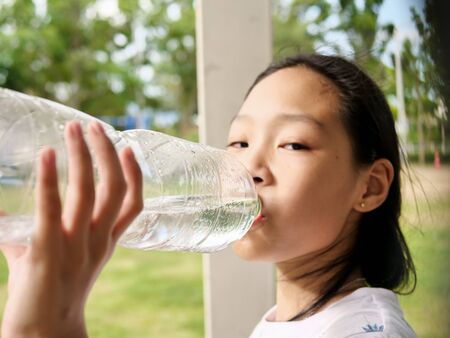Photo for Asian girl drinking a bottle of water outdoor. - Royalty Free Image