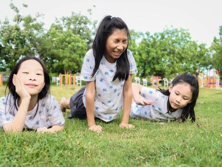 Photo pour Happy Asian girls laying down on green grass outdoor together, lifestyle concept. - image libre de droit