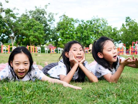 Happy Asian girls laying down on green grass outdoor together, lifestyle concept.
