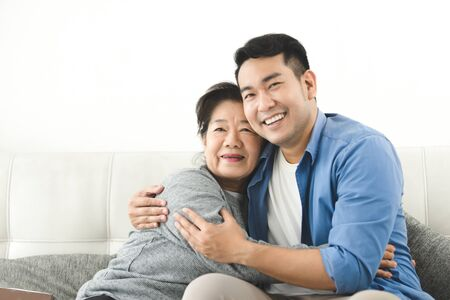 Foto de Asian mother hugging her son and sitting on sofa at home, lifestyle concept. - Imagen libre de derechos