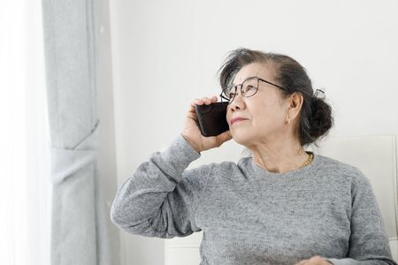 Foto per Asian senior woman make a phone call white sitting on sofa at home, lifestyle concept. - Immagine Royalty Free