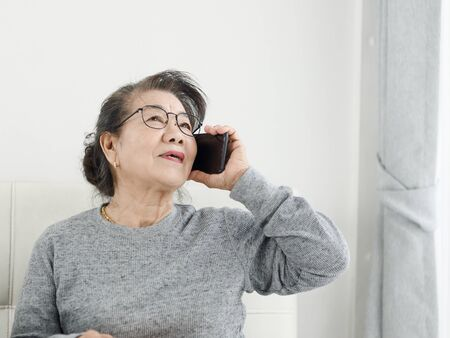 Photo for Asian senior woman make a phone call white sitting on sofa at home, lifestyle concept. - Royalty Free Image