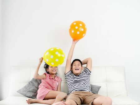 Foto de Asian sister and her brother playing balloons at home together, lifestyle concept. - Imagen libre de derechos