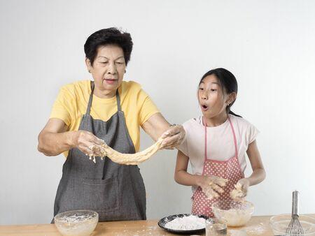 Photo pour Asian senior woman and girl making dough for homemade pizza or bread, lifestyle concept. - image libre de droit