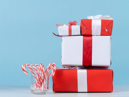 Photo for Red and white gift boxes and Christmas candy sticks on wooden table with blue wall. - Royalty Free Image