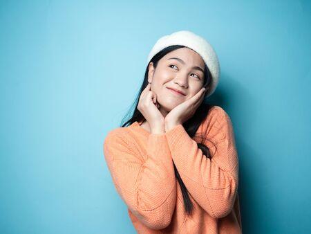 Foto de Asian woman wearing orange sweater on blue background, lifestyle concept. - Imagen libre de derechos