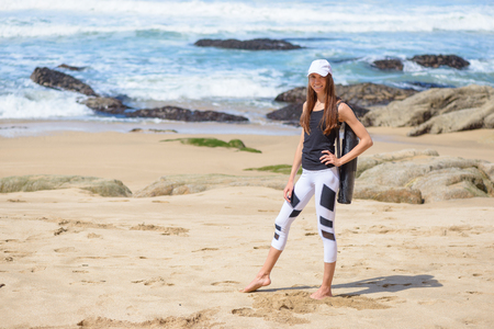Smiling active young woman in sports clothes on the beach