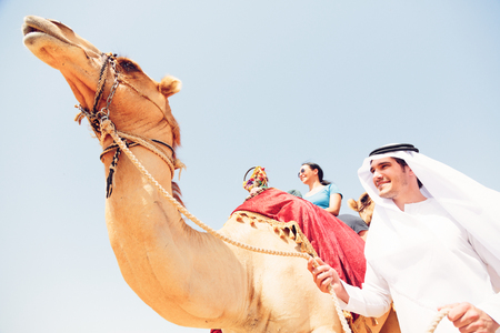 Photo for Arabian Man And Tourist Riding A Camel - Royalty Free Image