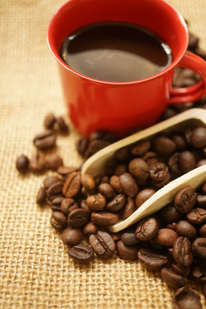 coffee beans , a scoop and coffee in a red cup
