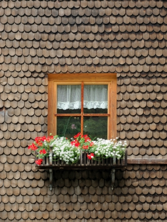 ancient wooden window with flowers surrounded by timber shingles
