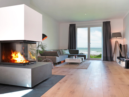 Photo pour modern living room with fireplace and a view to the sea - image libre de droit