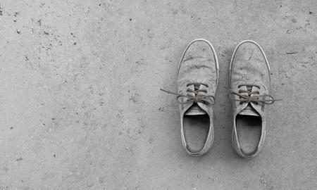Foto de camouflage pair of old grungy shoes on concrete background with copy space - Imagen libre de derechos