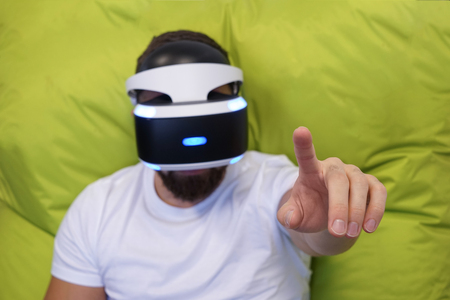 Photo pour Adult man with beard lying on his back in the virtual glasses on a green background, one hand lifted up, finger touches cyberspace, shallow depth of field, selective focus - image libre de droit