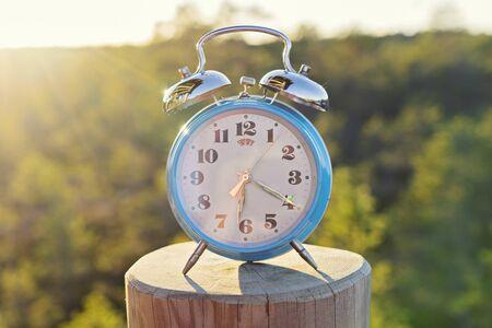 Photo pour Vintage blue alarm clock on summer forest background. Daylight saving time concept winter time - image libre de droit