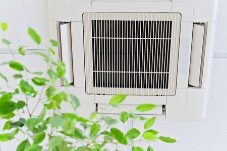 Photo pour Ceiling air conditioner in modern office or at home with green ficus plant leaves an idea of clean air. Indoor air quality concept - image libre de droit