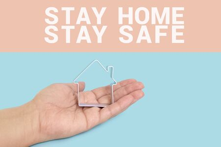Photo pour Inscription STAY SAFE and STAY HOME with house in hand palm on blue background. Motivation banner for self-isolation during coronavirus pandemic covid-19 - image libre de droit