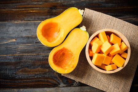 Foto per Half and slice butternut squash in bowl for cooking on wooden background, top view - Immagine Royalty Free
