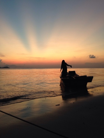 A woman standing on a boat, eagerly waiting for the sunrise