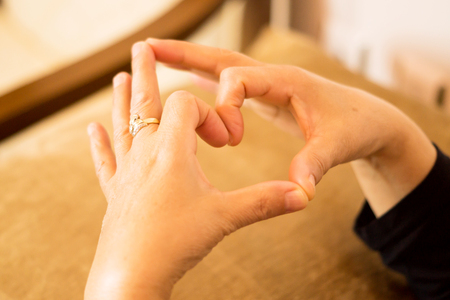 The expression of love making heart sign with fingers