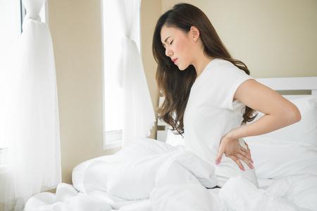 Photo pour Asian woman have a backache in bedroom morning because sleep problem - image libre de droit