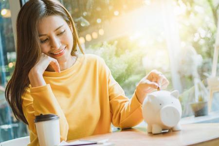 Photo pour Asian woman saving money and dropping coin to piggy - image libre de droit